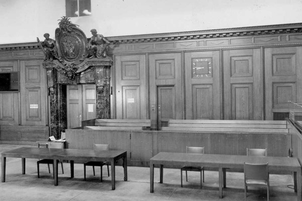 Blick auf die Anklagebänke vor Rückgabe des Schwurgerichtssaals 600 an die deutsche Justiz 1961. Die beiden Anklagebänke auf der rechten Seite, die nicht überliefert sind, waren deutlich breiter. Auf ihnen mussten jeweils sechs Angeklagte Platz nehmen.