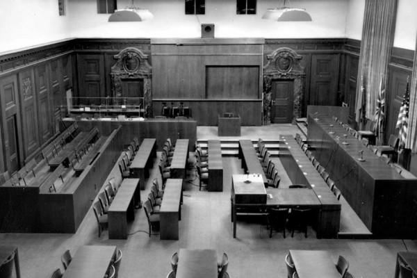 Blick von der Pressetribüne in den für den Prozess 1945 umgebauten Schwurgerichtssaal 600. Auf den Rückenlehnen der Anklagebänke sind die Kopfhörer zu sehen, die von den Angeklagten genutzt wurden, um das simultan in vier Sprachen übersetzte Prozessgeschehen zu verfolgen. Bildnachweis: Stadtarchiv Nürnberg